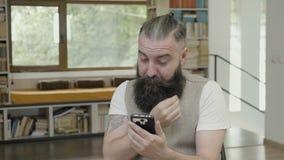 Hombre de negocios soñoliento con la reacción de la barba cuando él intenta leer el bostezo y el foco en su pantalla del smartpho almacen de video