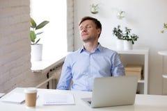 Hombre de negocios soñoliento con los ojos cerrados que se relajan en el lugar de trabajo fotografía de archivo libre de regalías