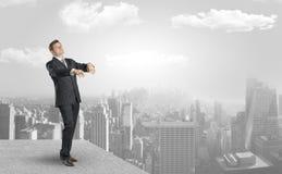 Hombre de negocios soñoliento en el top de la ciudad foto de archivo