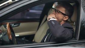 Hombre de negocios soñoliento que bosteza en el coche, sosteniendo la botella de vino, resaca, riesgo de accidente almacen de metraje de vídeo