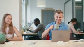 Hombre de negocios soñoliento que pone con el ordenador portátil en coworking El decir del hombre joven le agradece metrajes