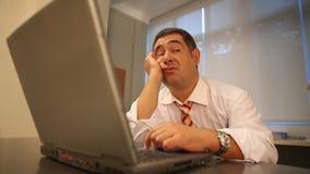 Hombre de negocios soñoliento usando el ordenador portátil en oficina almacen de metraje de vídeo