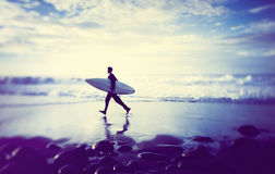 Hombre de negocios solitario por la playa con la tabla hawaiana Fotografía de archivo