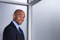 Hombre de negocios sonriente al lado de una ventana fotografía de archivo libre de regalías