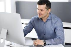 Hombre de negocios sonriente alegre que trabaja con el ordenador en oficina moderna Headshot del empresario o del director de sex fotografía de archivo libre de regalías