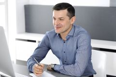 Hombre de negocios sonriente alegre que trabaja con el ordenador en oficina moderna Headshot del empresario o del director de sex imagen de archivo libre de regalías