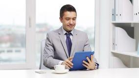 Hombre de negocios sonriente con café de consumición de la PC de la tableta almacen de metraje de vídeo