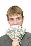 Hombre de negocios sonriente con centenares de dólares Imagenes de archivo