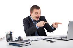 Hombre de negocios sonriente con el ordenador portátil y documentos en la oficina imagen de archivo libre de regalías