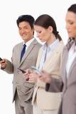 Hombre de negocios sonriente con el teléfono móvil al lado de colegas Fotos de archivo libres de regalías