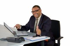 Hombre de negocios sonriente con la computadora portátil que presenta los pulgares para arriba Foto de archivo libre de regalías
