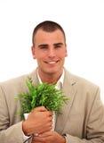 Hombre de negocios sonriente con una planta imagen de archivo libre de regalías