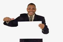 Hombre de negocios sonriente con una tarjeta que presenta los pulgares para arriba Fotografía de archivo