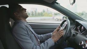 Hombre de negocios sonriente de la raza mixta que practica surf medios sociales en su tableta que se sienta dentro de su coche