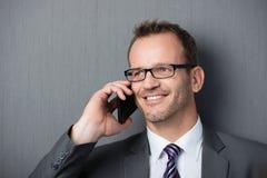 Hombre de negocios sonriente en el teléfono móvil Imagen de archivo libre de regalías
