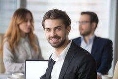 Hombre de negocios sonriente en el traje que mira la cámara que presenta en el encuentro fotografía de archivo libre de regalías