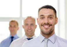 Hombre de negocios sonriente en oficina con la parte posterior del equipo encendido Imagen de archivo