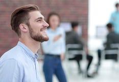 Hombre de negocios sonriente en perfil en fondo de la oficina, foto de archivo