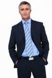 Hombre de negocios sonriente en traje con las manos en la presentación del bolsillo Fotos de archivo libres de regalías