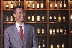 Hombre de negocios sonriente en un traje que hace una pausa una pared con las botellas de vino Fotos de archivo libres de regalías