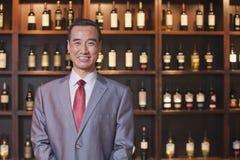 Hombre de negocios sonriente en un traje que hace una pausa una pared con las botellas de vino, retrato Imágenes de archivo libres de regalías