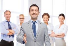 Hombre de negocios sonriente feliz en el traje que sacude la mano fotografía de archivo