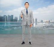 Hombre de negocios sonriente feliz en el traje que sacude la mano imagen de archivo