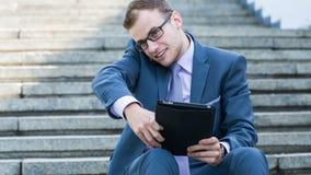 Hombre de negocios sonriente feliz joven que trabaja con la tableta, retrato horizontal. Foto de archivo