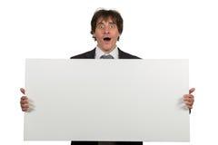 Hombre de negocios sonriente feliz que muestra el letrero en blanco, aislado sobre el fondo blanco Foto de archivo