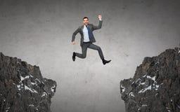 Hombre de negocios sonriente feliz que salta entre las rocas Fotos de archivo libres de regalías
