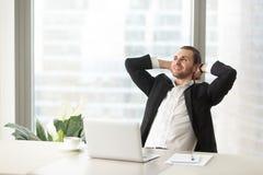 Hombre de negocios sonriente feliz que se relaja en el escritorio del trabajo en oficina moderna imagen de archivo libre de regalías