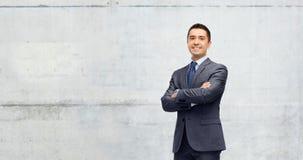 Hombre de negocios sonriente feliz sobre el muro de cemento gris foto de archivo