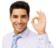 Hombre de negocios sonriente Gesturing Okay Foto de archivo libre de regalías