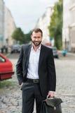 Hombre de negocios sonriente Holding Working Bag en la calle Foto de archivo libre de regalías