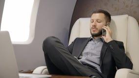 Hombre de negocios sonriente joven del abogado que habla en el teléfono que se sienta en la primera clase de aeroplano del empres metrajes