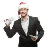 Hombre de negocios sonriente joven en el sombrero de santa que sostiene el dinero Foto de archivo libre de regalías