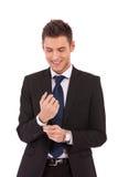Hombre de negocios sonriente que abotona su funda fotos de archivo libres de regalías