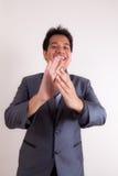 Hombre de negocios sonriente que aplaude sus manos imagenes de archivo