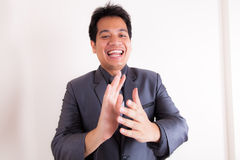 Hombre de negocios sonriente que aplaude sus manos fotos de archivo