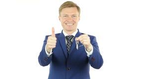 Hombre de negocios sonriente que da llaves de la casa, oficina almacen de video