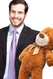 Hombre de negocios sonriente que da un oso de peluche fotografía de archivo