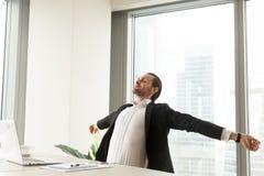 Hombre de negocios sonriente que estira en el lugar de trabajo en oficina moderna imágenes de archivo libres de regalías