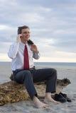 Hombre de negocios sonriente que hace una llamada de teléfono en una playa fotografía de archivo libre de regalías