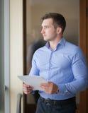 Hombre de negocios sonriente que hace una pausa la ventana en oficina y la lectura Fotografía de archivo libre de regalías