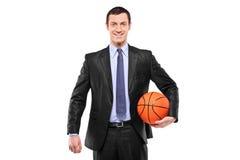 Hombre de negocios sonriente que lleva a cabo un baloncesto Imagenes de archivo