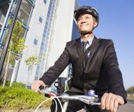 Hombre de negocios sonriente que monta una bicicleta al lugar de trabajo Fotos de archivo