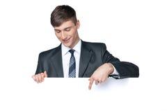 Hombre de negocios sonriente que muestra algo en el cartel en blanco. Fotografía de archivo