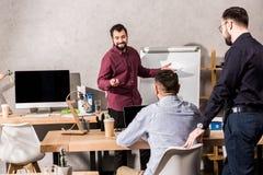 hombre de negocios sonriente que muestra algo a los colegas en el flipchart en oficina imágenes de archivo libres de regalías