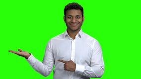 Hombre de negocios sonriente que presenta el lugar para su texto o producto almacen de metraje de vídeo