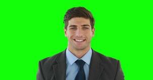 Hombre de negocios sonriente que presenta para la cámara almacen de video